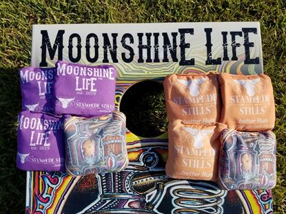 Stampede Stills Moonshine Life™ STILL YOUR FACE graphic PRO Cornhole bags Purple vs Orange
