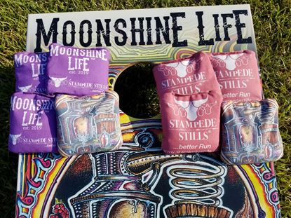 Stampede Stills Moonshine Life™ STILL YOUR FACE graphic PRO Cornhole bags Purple vs Red